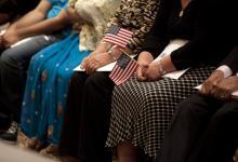Immigrants holding American flags as they become citizens with the help of ACCESS services.