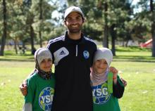 Volunteer coach with two children.